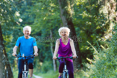 happy and active senior couple riding