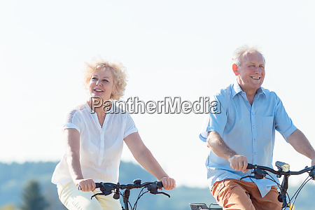 active elderly couple riding bicycles together