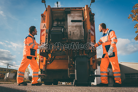 two refuse collection workers loading garbage