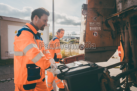 garbage man and women cleaning dustbins