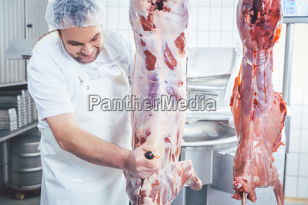 butcher cutting to pieces meat from
