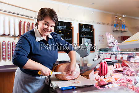 experienced butcher shop assistant cutting ham