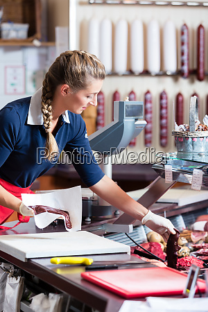 sales woman in butcher shop putting
