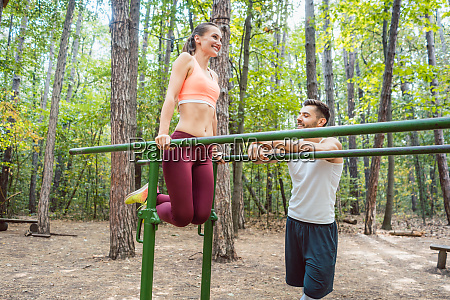 fit woman exercising on parallel bar