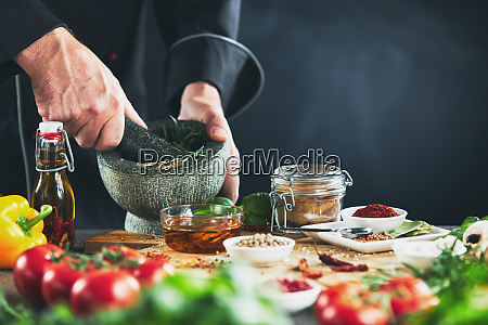 chef grinding herbs in a pestle