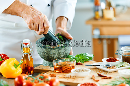 man using pestle to grind food