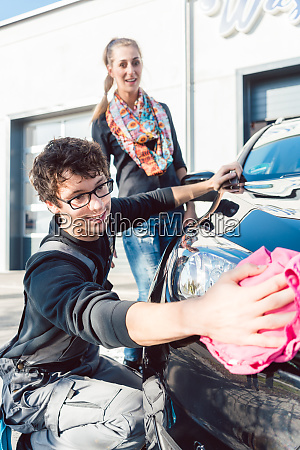 service man cleaning lamp of vehicle