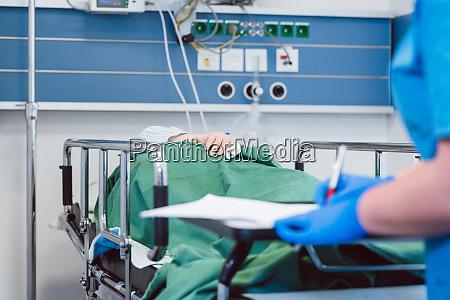 nurse writing down data on patient