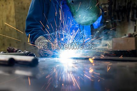 welder in his workshop welding metal