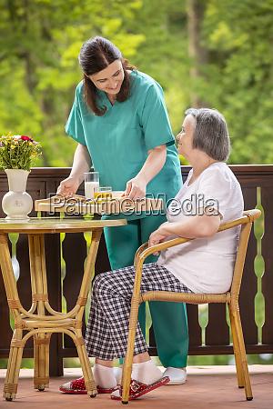 nurse serving healthy breakfast to happy