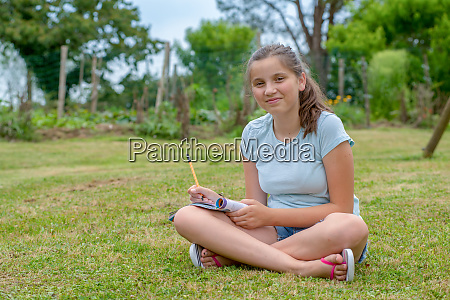 young and smiling teenager sitting cross