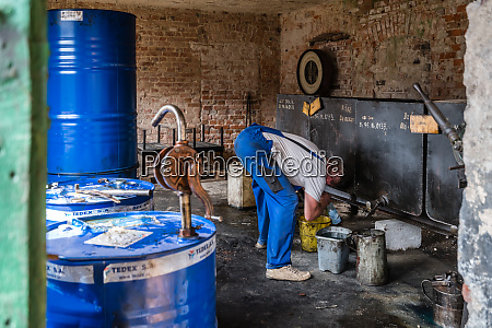 worker filling bucket with oil