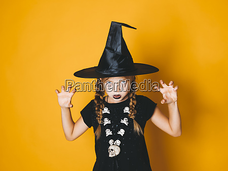 young halloween witch on orange background