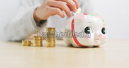 putting golden coins into piggy bank