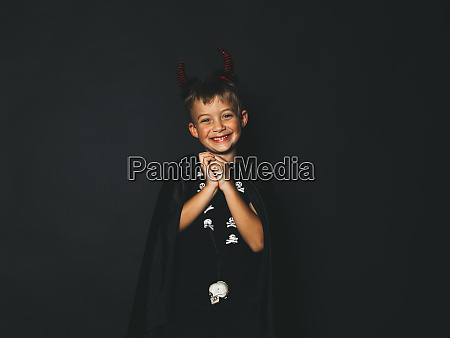 little boy with red halloween horns