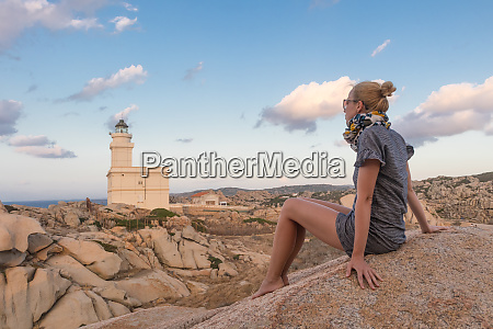 solitary young female traveler watches a