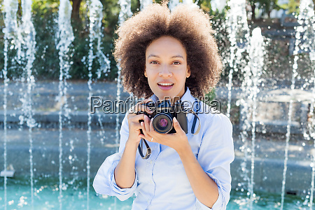 charming black woman with retro camera