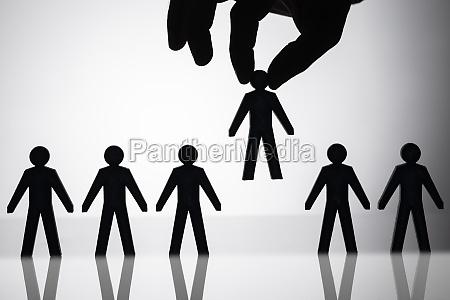 person picking up human figure amongst