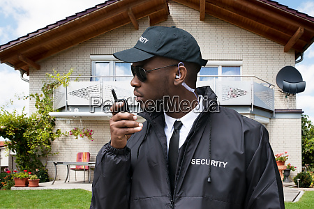 african male security guard talking on