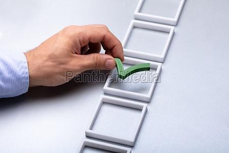 man placing check mark in box