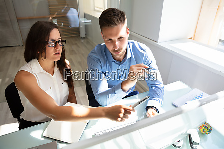 two businesspeople looking at computer having