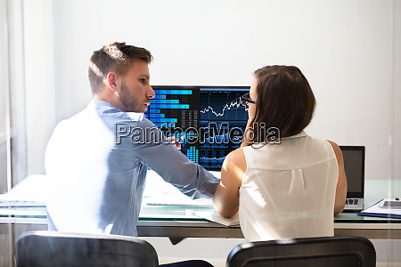 two stock market brokers discussing graphs