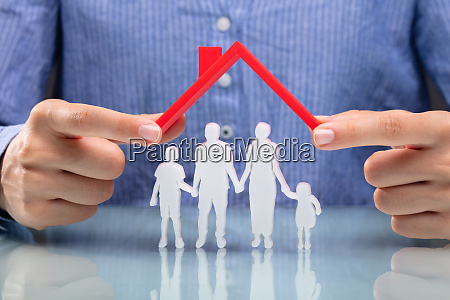 businesswoman protecting family figures with red