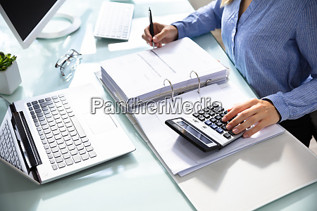 businesswomans hand calculating bill in office