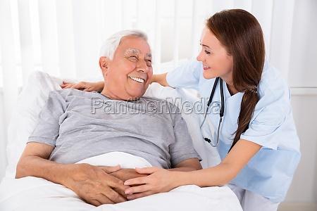 nurse looking at happy male patient