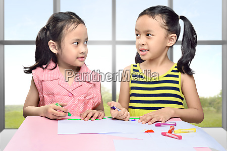 smiling two asian girl with crayon