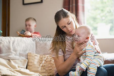 mother burping her newborn baby