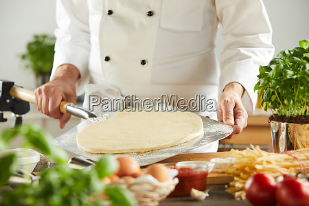 italian chef making traditional pizza