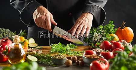 man chopping herb leaves on cutting