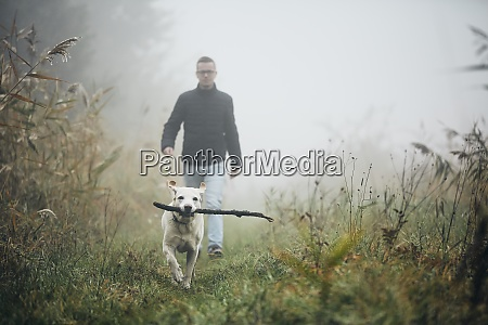 man walking with dog in autumn