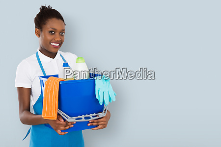 smiling female janitor holding cleaning equipment