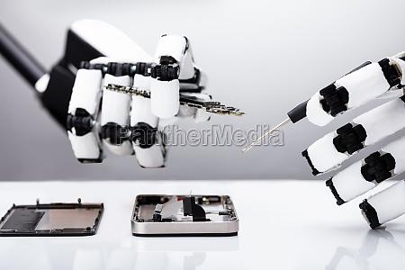 robot repairing smartphone with screwdriver