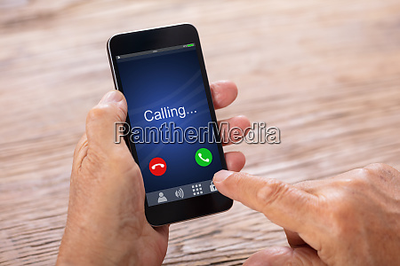 man holding smartphone with incoming call