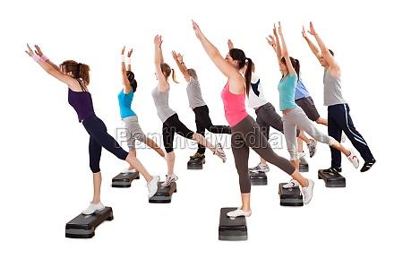 class doing aerobics balancing on boards