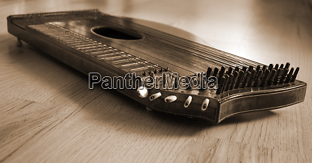 old zither lying on a wooden