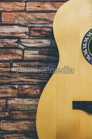 acoustic guitar on a brick wall