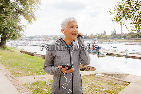 senior woman listening music after running