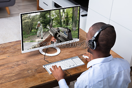 man playing action game on computer