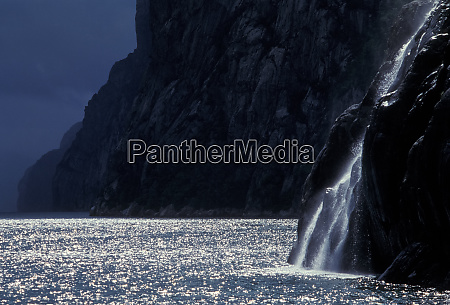 norwegian fjord with backlit waterfall