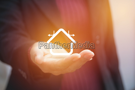 hand of businesswoman holding house icon