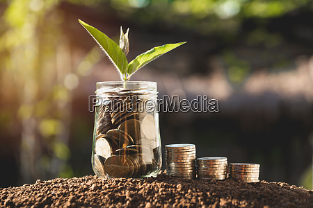 coins in jar with money stack