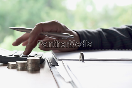 man using calculator with stock financial