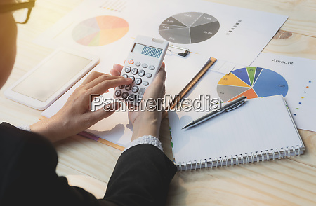 businesswoman using calculator with stock financial