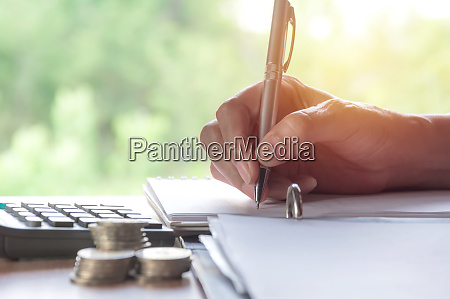 man writing with stock financial indices