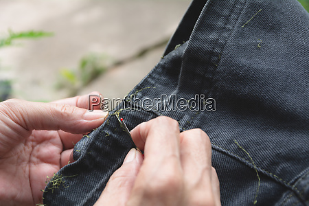 hand holding and using sewing seam