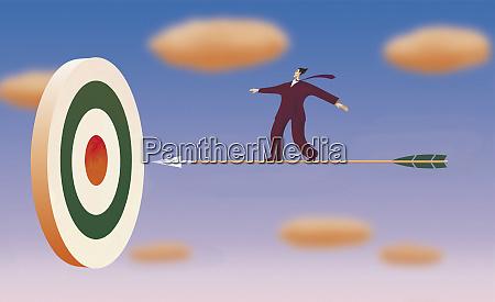 businessman on arrow flying towards target